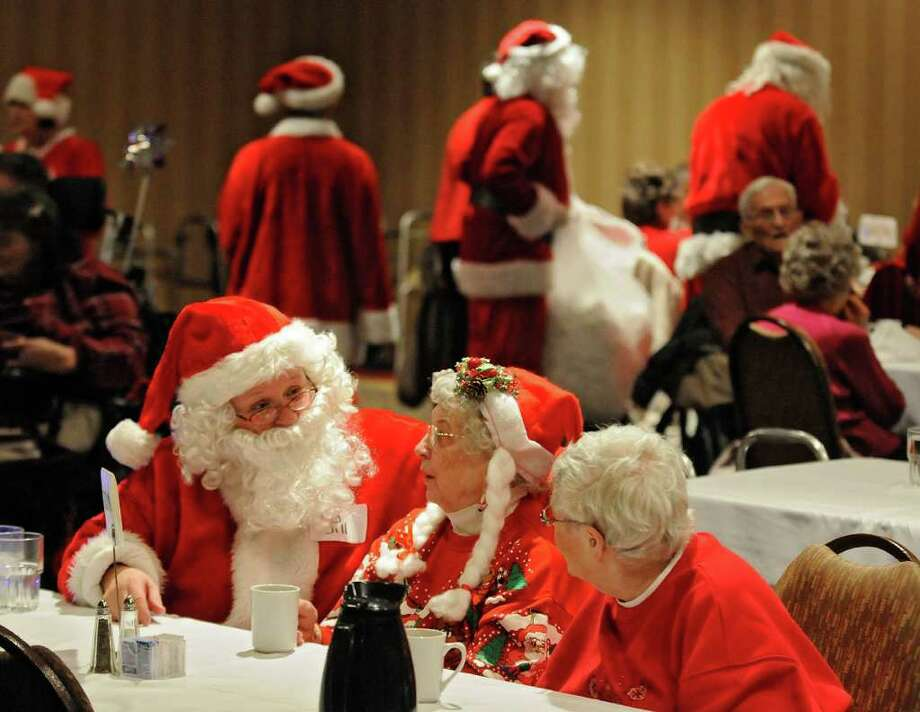 Santa Jill Schultz talks to Margaret Henning and Shirley Nord during the Dinner With Santa event Thursday, Dec. 15, 2011, at the St. Cloud, Minn., Holiday Inn. Dozens of volunteers dressed as Santa served meals to seniors from throughout the area. This year marked the 26th for the event. Photo: Dave Schwarz, Associated Press / St. Cloud Times