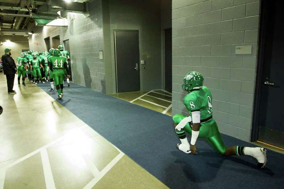 Hempstead quarterback Obie Wilder (8) stretches in a service corridor at the stadium before the 2A Div. I state championship high school football game at Cowboys Stadium Thursday, Dec. 15, 2011, in Arlington. Photo: Smiley N. Pool, Houston Chronicle / © 2011  Houston Chronicle