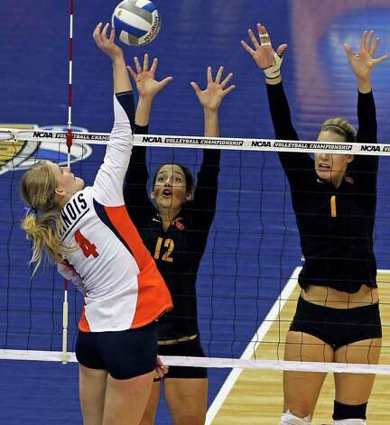 SPORTS   Colleen Ward gets up for a kill over Trojan players Kendall Bateman (12) and Alexis Olgard as Illinois plays USC  in a  2011 NCAA National Semifinal match at the Alamodome on December 15, 2011 Tom Reel/Staff Photo: TOM REEL, SAN ANTONIO EXPRESS-NEWS / © 2011 San Antonio Express-News