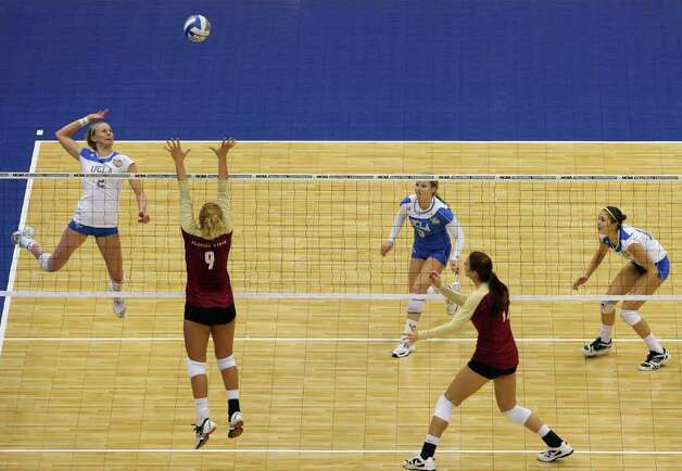 UCLA's Kelly Reeves (2) prepares to spike the ball as Florida State's Visnja Djurdjevic (9) defends during game action of the 2011 NCAA Division I Women's Volleyball Championship National Semifinal Match #1 at the Alamodome on Thursday, Dec. 15, 2011. MICHAEL MILLER / mmiller@express-news.net Photo: MICHAEL MILLER, Express-News / mmiller@express-news.net