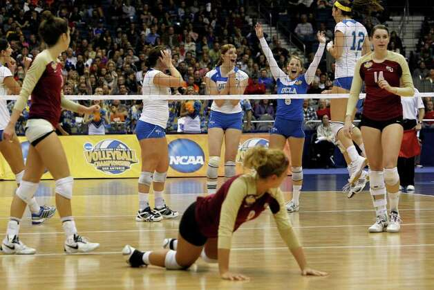 Florida State's Visnja Djurdjevic, bottom center, gets up after a point as UCLA's Rachael Kidder (11), Lainey Gera (06) and Mariana Aquino (12) celebrate during game action of the 2011 NCAA Division I Women's Volleyball Championship National Semifinal Match #1 at the Alamodome on Thursday, Dec. 15, 2011. MICHAEL MILLER / mmiller@express-news.net Photo: MICHAEL MILLER, Express-News / mmiller@express-news.net