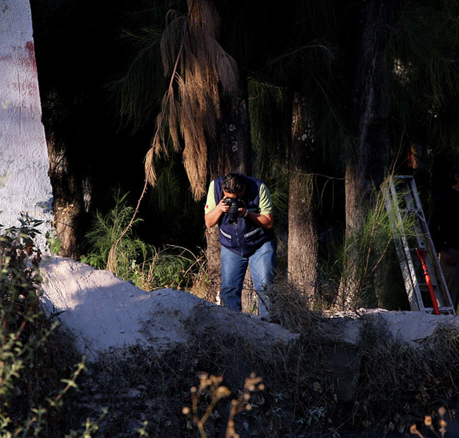 Forensic personnel work on a clandestine grave found in the  garden of the Federation of Students of Guadalajara headquarters, in  Guadalajara, Mexico, on December 15, 2011. The bodies of five people were  unearthed when authorities started investigations after four students and the  father of one of them was reported missing since five days ago.  Photo: (HECTOR GUERRERO/AFP/Getty Images)