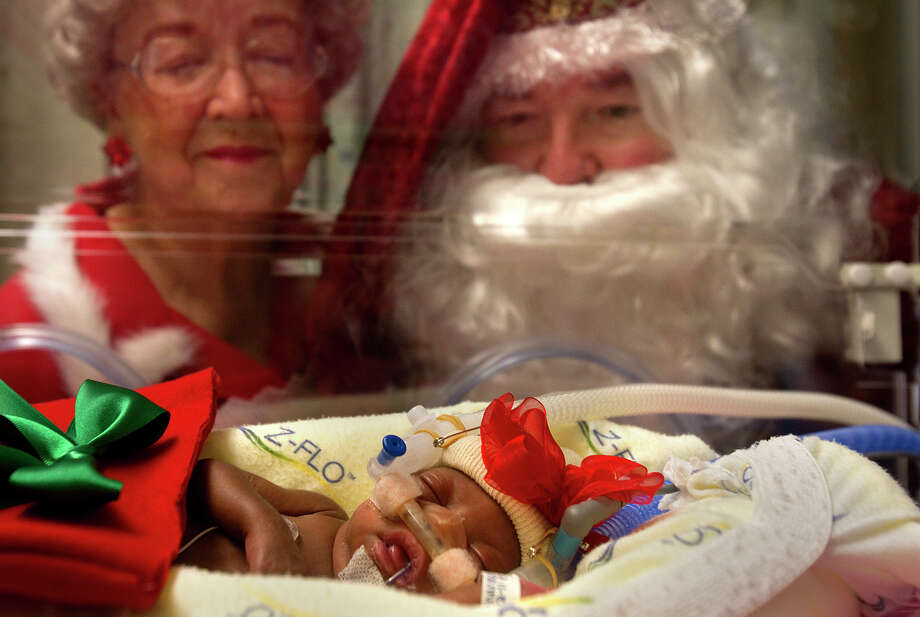Santa and Mrs. Claus watch as  44-day-old Kaidyn Richardson rests in an isolette at Memorial Hermann  Southwest Friday,  Dec. 16,  2011,  in Houston. The tiny patients at the  hospital got their first photos with Santa and Mrs. Claus. (Cody Duty/Houston Chronicle) / © 2011 Houston Chronicle