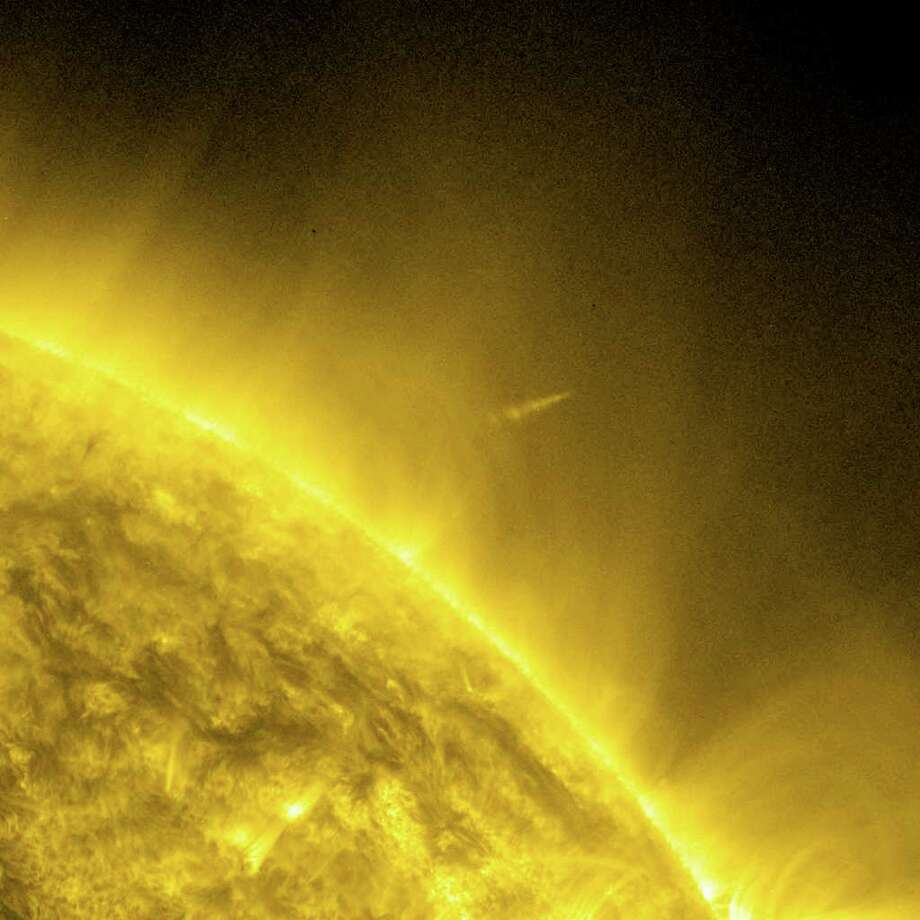 This handout image provided by NASA's Solar Dynamics Observatory, taken, Thursday shows the Comet Lovejoy leaving the sun's corona which is several million degrees. A small comet survived what astronomers figured would be a sure death when it danced uncomfortably close to the broiling sun Thursday night. Comet Lovejoy, which was only discovered a couple of weeks ago, was supposed to melt as it came so close to the sun that the temperatures around it would hit several million degrees. Astronomers had tracked 2,000 other sun-grazing comets make the same suicidal trip. None had ever survived. Photo: AP