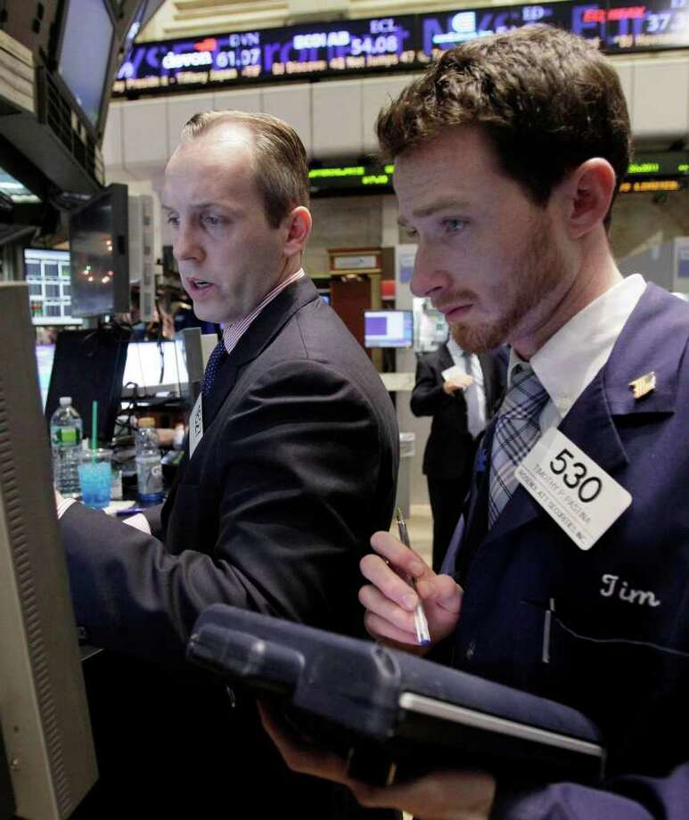 In this Dec. 15, 2011 photo, specialist Patrick Kenny, left, and trader Timothy Pastina work on the floor of the New York Stock Exchange. World stocks were buoyed Friday, Dec. 16, by improving U.S. economic indicators and the expected approval in Italy of an austerity plan intended to get the country's finances under control. (AP Photo/Richard Drew) Photo: Richard Drew / AP