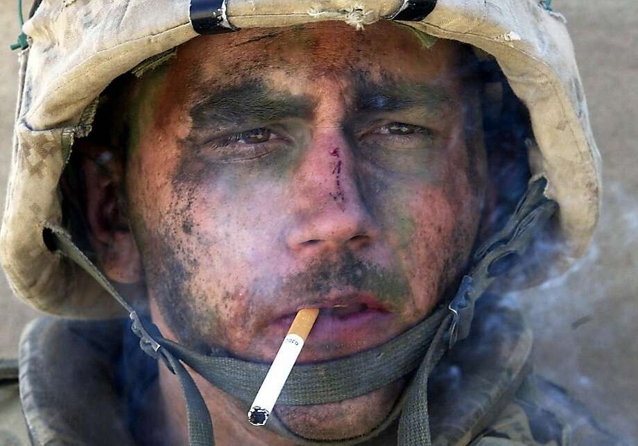 "**ADVANCE FOR SUNDAY, MARCH 9--FILE** Marine Lance Cpl. James Blake Miller, 20, of Kentucky, a member of Charlie Company of the U.S. Marines First Division, Eighth regiment, smokes a cigarette in Fallujah, Iraq, in this Nov. 9, 2004 file photo. Miller came to be known as the ""Marlboro Man"" for this iconic photograph from the Iraq War. (AP Photo/Los Angeles Times, Luis Sinco, file) ** MANDATORY CREDIT, NO SALES, NO FOREIGNS, MAGS OUT ** Ran on: 03-09-2008 Scenes such as this Iraqi man comforting his 4-year-old son near Najaf were common sights for American soldiers. Photo: Luis Sinco, AP"