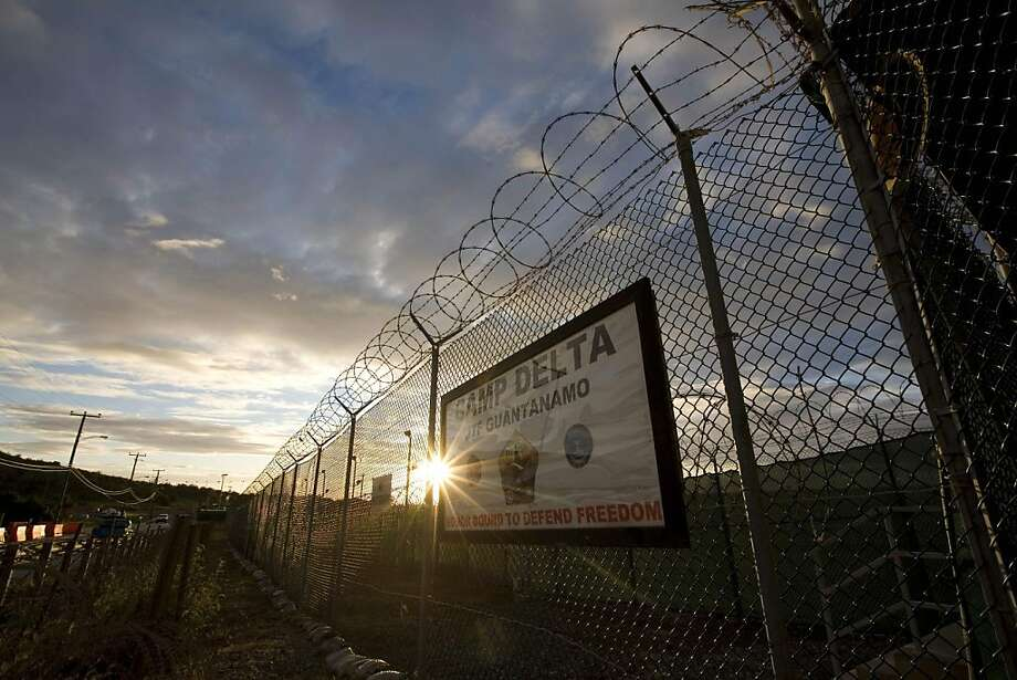 In this image reviewed by the U.S. Military, the sun rises behind a sign at Guantanamo detention facility at the U.S. Naval Base in Guantanamo Bay, Cuba, Tuesday, Nov. 18, 2008. The U.S. has used loud music against those held in Guantanamo Bay, Iraq and Afghanistan, and detainees now aren't the only ones complaining: Musicians are banding together to demand the U.S. military stop using their songs as weapons. (AP Photo/Brennan Linsley) Ran on: 12-10-2008 At Guantanamo, music treatment was once called common; the commander says it's not used now. Photo: Brennan Linsley, AP