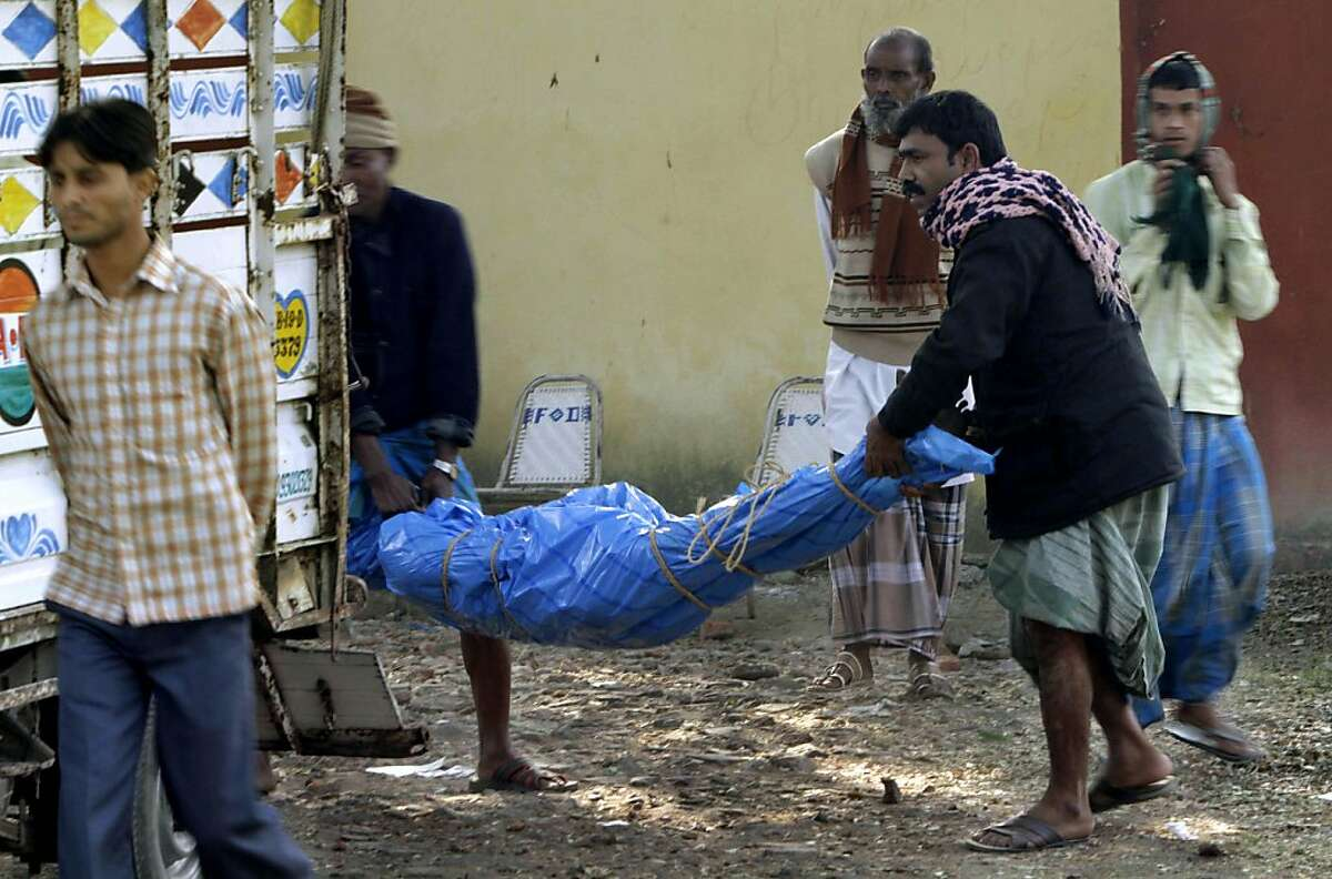 People prepare to place the body of a toxic liquor victim onto a truck outside a hospital in Diamond Harbour, near Kolkata, India, Thursday, Dec. 15, 2011. Bootleg liquor laced with toxic methanol killed scores of people and sickened dozens more who bought the illegal brew at small shops in eastern India, officials said Thursday.(AP Photo/Bikas Das)