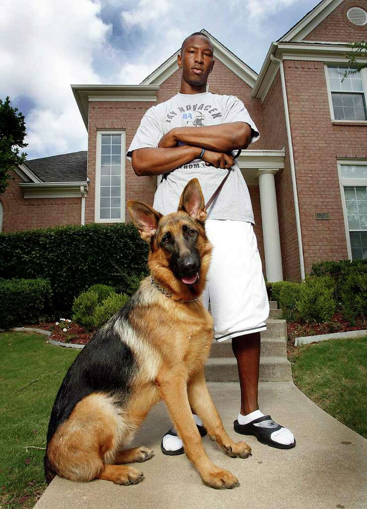 Dallas Cowboy wide receiver Sam Hurd poses with his German shepherd watchdog Butch in front of his in Irving home on June 25, 2008.