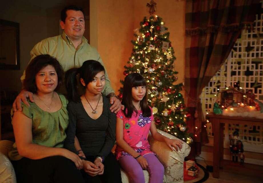 La familia Salgado: Bettina, sentada con sus hijas, Priscilla y Jennifer, y Martín, el padre, decidieron no viajar a México por Navidad. Photo: Mayra Beltran / © 2011 Houston Chronicle