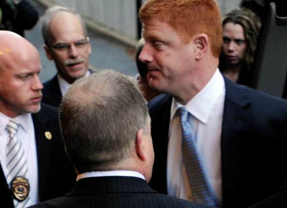 Penn State assistant football coach Mike McQueary, right, arrives at Dauphin County Court surrounded by heavy security Friday, Dec 16, 2011, in Harrisburg, Pa. McQueary declined to speak to reporters Friday as he entered the courthouse in Harrisburg for the hearing for Gary Schultz and Tim Curley, who are set to appear for a preliminary hearing related to the Jerry Sandusky child sex abuse case. (AP Photo/Bradley C Bower) Photo: Bradley C. Bower / FR37962 AP