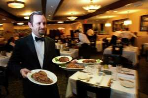 Ron Slater delivers food during lunch at Morton's The Steakhouse Friday, Dec. 16, 2011, in Houston.