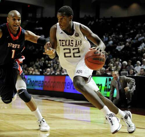 Texas A&M forward Khris Middleton (22) drives the ball around Dallas Baptist forward Jordan McGowen (1) during the first half of an NCAA college exhibition basketball game on Thursday, Nov. 3, 2011, in College Station, Texas. Photo: AP