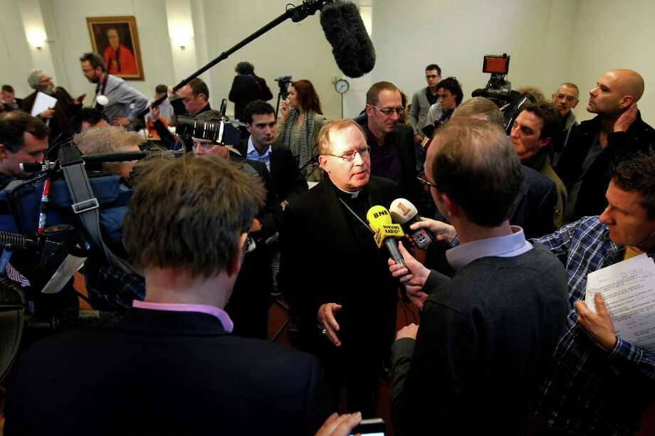 """BAS CZERWINSKI: ASSOCIATED PRESS UNDER FIRE: Archbishop of Utrecht Wim Eijk, center, answers questions during a news conference in which he said the report on sexual abuse """"fills us with shame and sorrow."""" Photo: BAS CZERWINSKI / AP"""