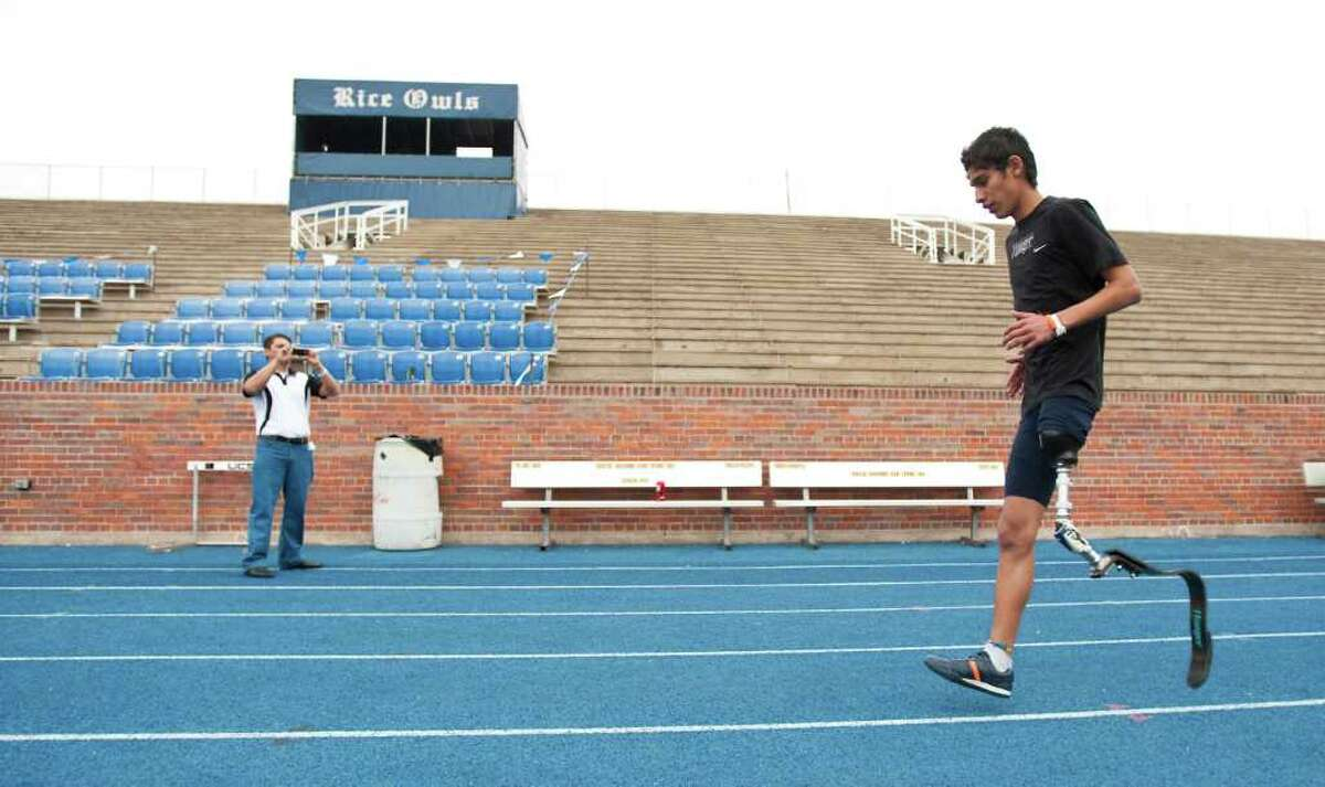 Alan Sanchez, 17, of Monterey, Mexico, tries out a new above knee prosthetic designed for running as his father Francisco Sanchez makes a video at Rice University.