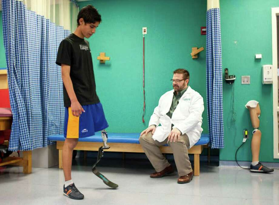 Alan Sanchez, 17, of Monterey, Mexico, jumps around for Jason Jennings, of Dynamic Orthotics and Prosthetics as he's fitted for a new above knee prosthetic designed for running. Photo: Nick De La Torre, Houston Chronicle / © 2011  Houston Chronicle