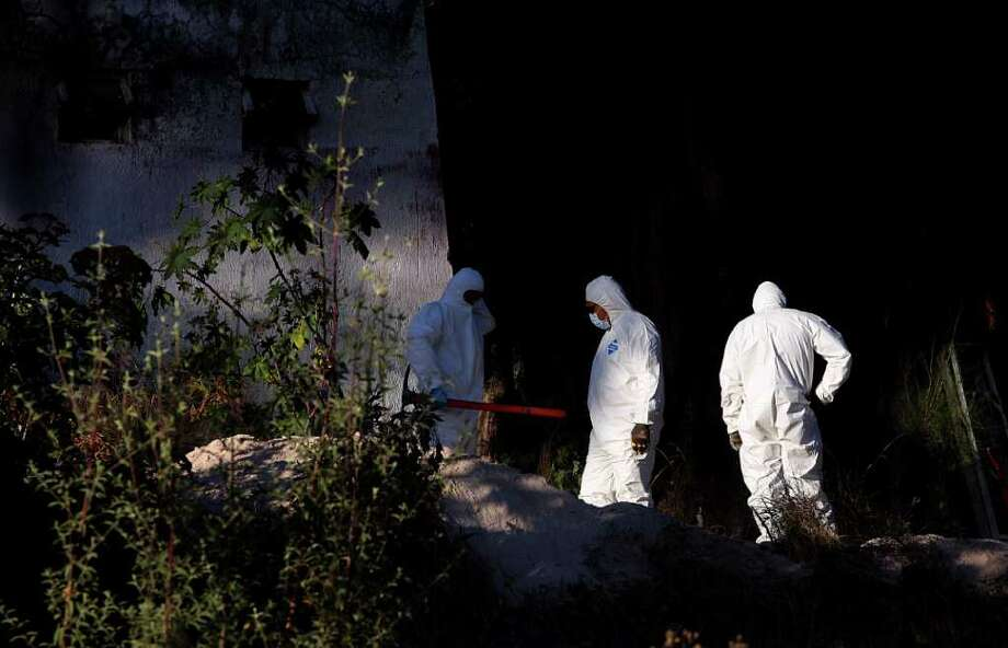 Forensic personnel work at a grave found in the garden of the Guadalajara Student Federation headquarters Thursday in Guadalajara, Mexico. The bodies of four students and an adult were unearthed at the site. Photo: HECTOR GUERRERO / AFP