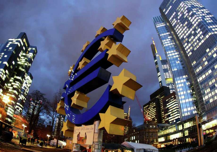 The Euro sculpture stands in front of the European Central Bank, right,  in Frankfurt, Germany, on Friday, Dec. 16, 2011.  Poster underneath the Euro sign reads: Let's talk about Future.(AP Photo/Michael Probst) Photo: Michael Probst / AP