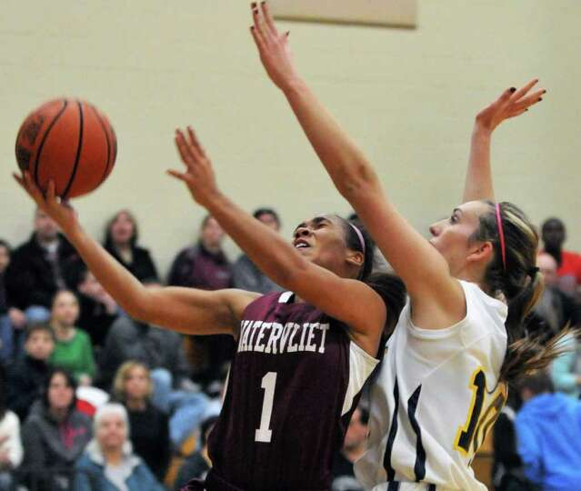 Watervliet's #1, Ailayia Demand, left, drives to the basket against Holy Names's #10 Mary Kate Meurr