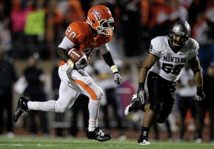 Sam Houston State running back Tim Flanders (20) runs past Montana linebacker John Kanongata'a (52)