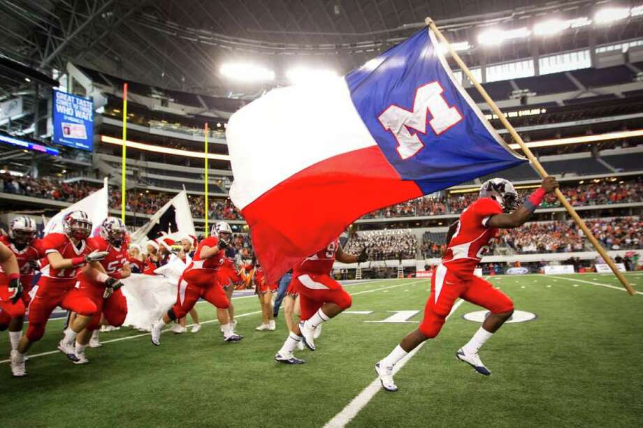 Manvel wide receiver Corey Seymour carries the school flag as he leads the Mavericks onto the field to face Aledo in the 4A Div. 2 state championship high school football game at Cowboys Stadium on Saturday, Dec. 17, 2011, in Arlington. Photo: Smiley N. Pool, Houston Chronicle / © 2011  Houston Chronicle