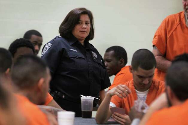 Officer Gloria Dehoyos works one of the units in the Bexar County Jail Annex, Thursday, December 15, 2011. Three months after Commissioners Court approved a 2012 budget that included losing 100 jail guards through attrition, Bexar County detention officers are now working mandatory overtime to man the 140 posts that guard about 3,600 inmates. Photo: JENNIFER WHITNEY, Jennifer Whitney/ Special To The Express-News / special to the Express-News
