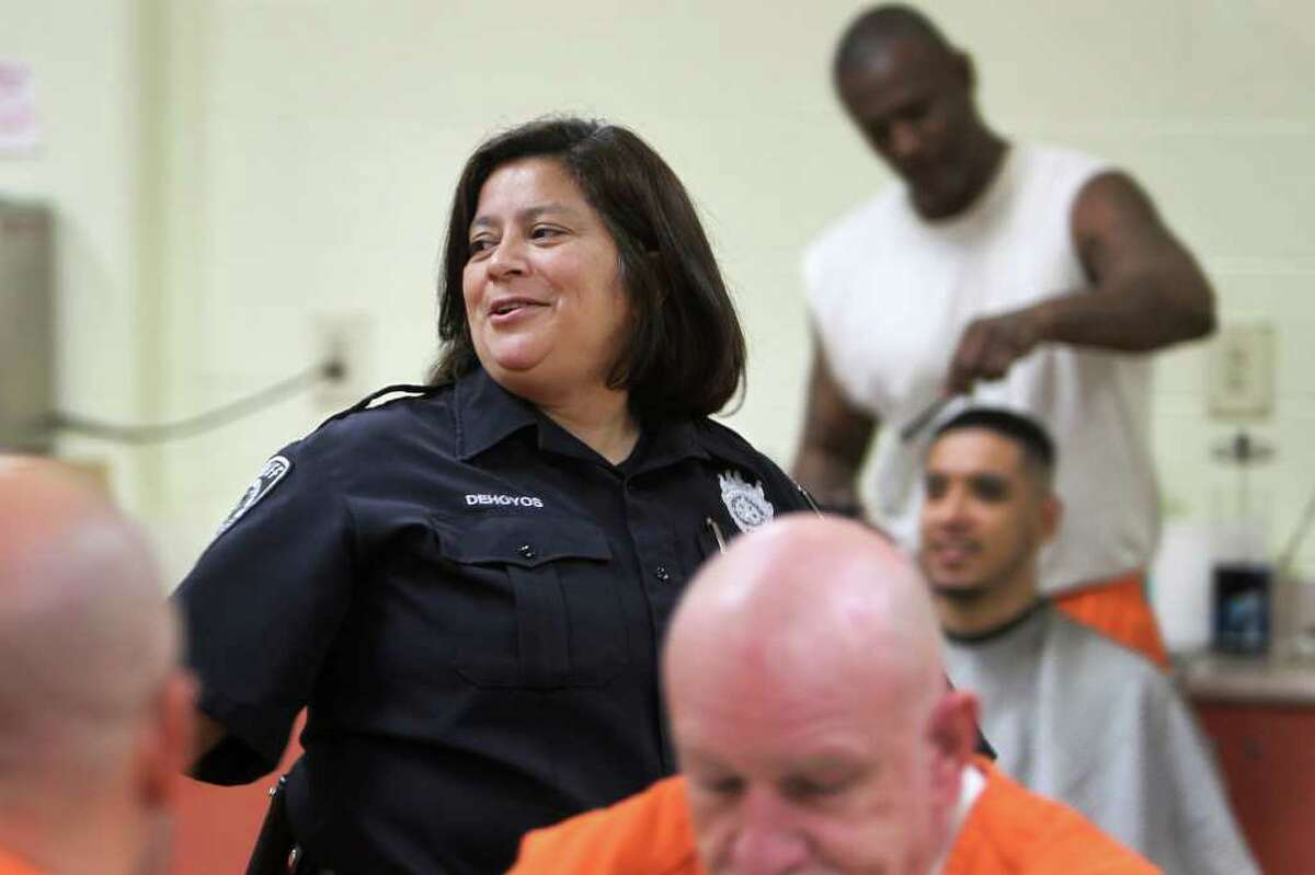 Officer Gloria Dehoyos works one of the units in the Bexar County Jail Annex, Thursday, December 15, 2011. Three months after Commissioners Court approved a 2012 budget that included losing 100 jail guards through attrition, Bexar County detention officers are now working mandatory overtime to man the 140 posts that guard about 3,600 inmates.