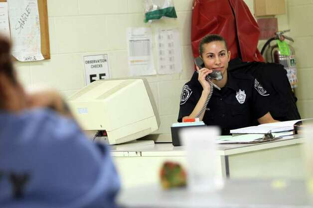 Officer Stacey Thompson works on disciplinary reports from an incident involving two combatives at her desk inside one of the units in the Bexar County Jail Annex, Thursday, December 15, 2011. Thompson, whose husband also works at the jail, has trouble juggling the extra hours with children at home. Three months after Commissioners Court approved a 2012 budget that included losing 100 jail guards through attrition, Bexar County detention officers are now working mandatory overtime to man the 140 posts that guard about 3,600 inmates. Photo: JENNIFER WHITNEY, Jennifer Whitney/ Special To The Express-News / special to the Express-News