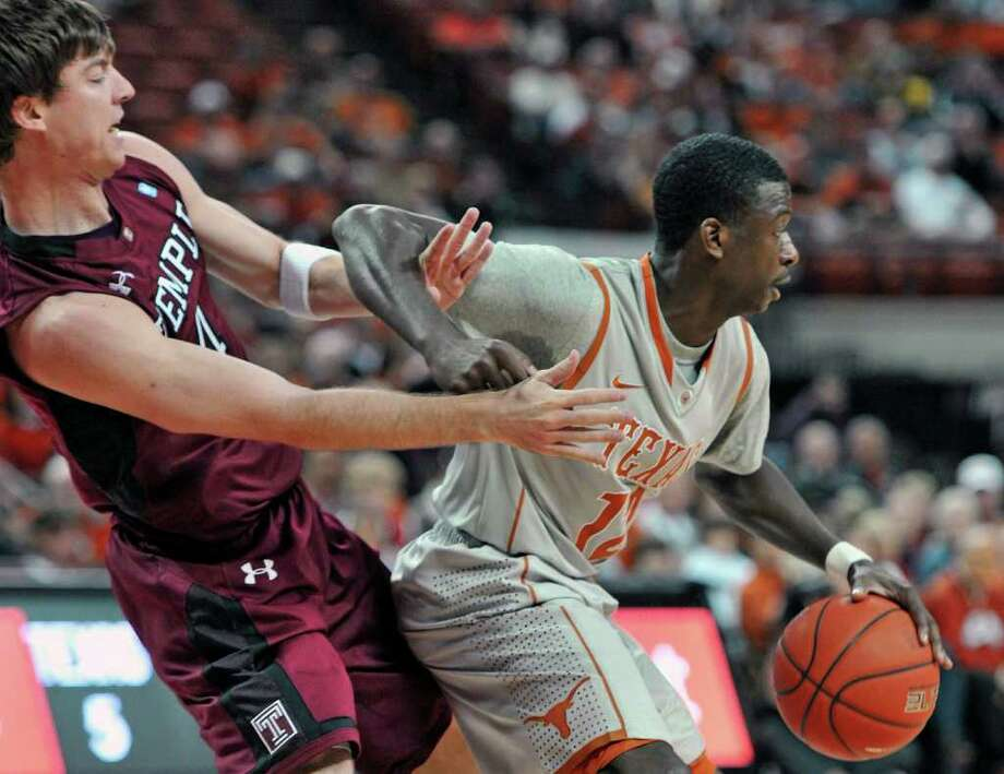 Temple guard Juan Fernandez, left, gets tangled up with Texas guard Myck Kabongo, right, during the first half of an NCAA college basketball game Saturday, Dec. 17, 2011, in Austin, Texas. (AP Photo/Michael Thomas) Photo: Michael Thomas, Associated Press / FR65778 AP
