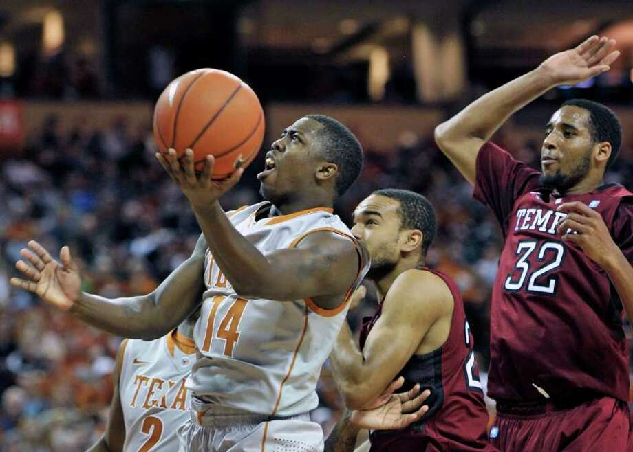 Texas guard J'Covan Brown, left, goes to the basket against Temple guard Aaron Brown, center, and forward Rahlir Hollis-Jefferson (32) during the first half of an NCAA college basketball game on Saturday, Dec. 17, 2011, in Austin, Texas. (AP Photo/Michael Thomas) Photo: Michael Thomas, Associated Press / FR65778 AP