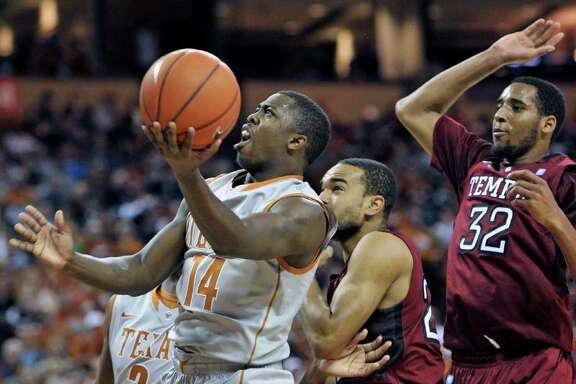 Texas guard J'Covan Brown, left, goes to the basket against Temple guard Aaron Brown, center, and forward Rahlir Hollis-Jefferson (32) during the first half of an NCAA college basketball game on Saturday, Dec. 17, 2011, in Austin, Texas. (AP Photo/Michael Thomas)