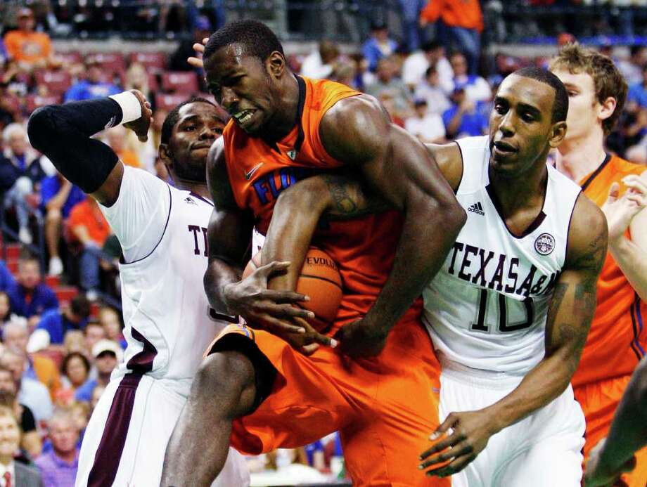 Florida's Patric Young, center, comes down with a rebound as he is pressured by Texas A&M forwards Ray Turner, left, and David Loubeau during the first half of an NCAA college basketball game, Saturday, Dec. 17, 2011, in Sunrise, Fla. (AP Photo/Wilfredo Lee) Photo: Wilfredo Lee, Associated Press / AP