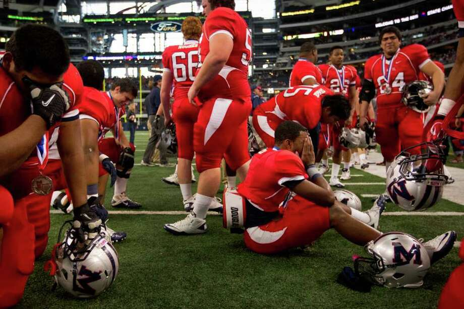 Manvel players collect themselves after the 4A Div. 2 state championship high school football game at Cowboys Stadium on Saturday, Dec. 17, 2011, in Arlington.  Aledo won the game 49-28. Photo: Smiley N. Pool, Houston Chronicle / © 2011  Houston Chronicle