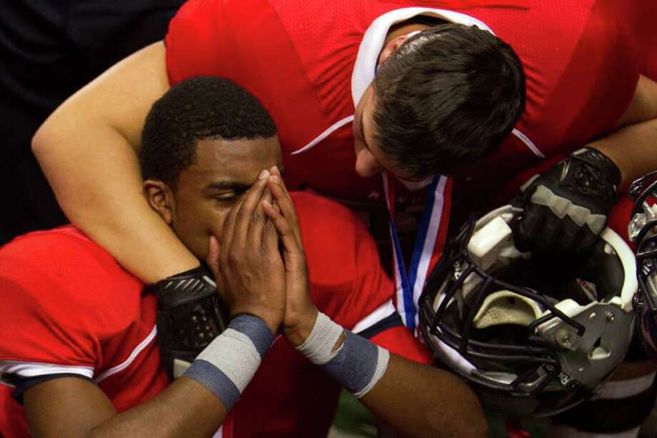 Manvel quarterback Julian Walker is consoled by offensive lineman Cory Klingler after the 4A Div. 2 state championship high school football game at Cowboys Stadium on Saturday, Dec. 17, 2011, in Arlington.  Aledo won the game 49-28. Photo: Smiley N. Pool, Houston Chronicle / © 2011  Houston Chronicle