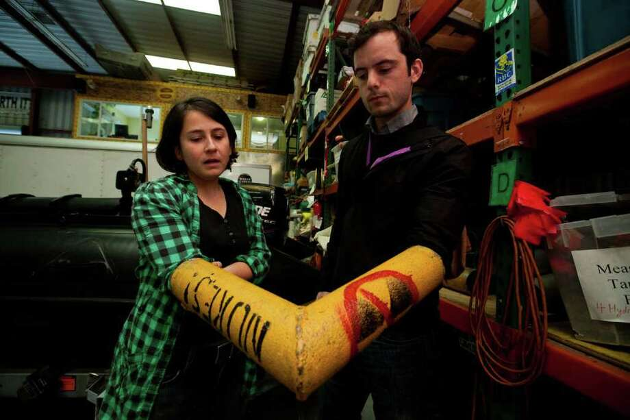ALEXIS CUAREZMA : LOS ANGELES TIMES TOGETHER TIME: Greenpeace's logistics manager, Hope Kaye, left, and spokesman James Turner demonstrate how a piece of pipe is used to interlock demonstrators' arms. Photo: Alexis Cuarezma / Los Angeles Times
