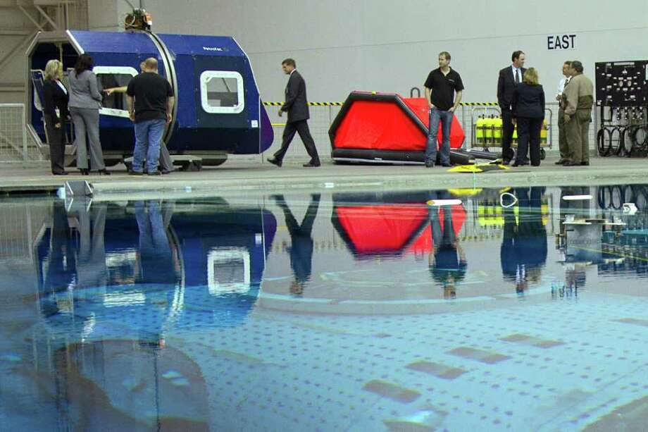 Representatives from NASA, Raytheon and Petrofac Training Services examine equipment used for the helicopter crash simulation at the Neutral Buoyancy Lab at the Sonny Carter Training Facility near the Johnson Space Center. Photo: Smiley N. Pool / © 2011  Houston Chronicle