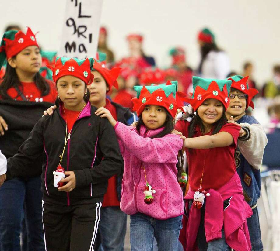 Pilgrim Academy student Simeona Tax, 8, left, leads her classmates Lindsey Juarez, 8, and Nallely Quiem, 9, to their circle of gifts during the Navidad En El Barrio Children's Events, at the George R. Brown Convention Center, Dec. 17, 2011, in Houston. 2,000 children from 50 area elementary schools were invited to take part in the annual Christmas event, which entertained the kids and they each were given gifts. Photo: Karen Warren, Houston Chronicle / © 2011 Houston Chronicle