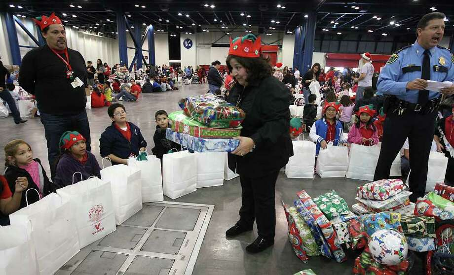 Irene McAlpine hands out presents to children from Pilgrim Academy during the Navidad En El Barrio Children's Events, at the George R. Brown Convention Center, Dec. 17, 2011, in Houston. Photo: Karen Warren, Houston Chronicle / © 2011 Houston Chronicle