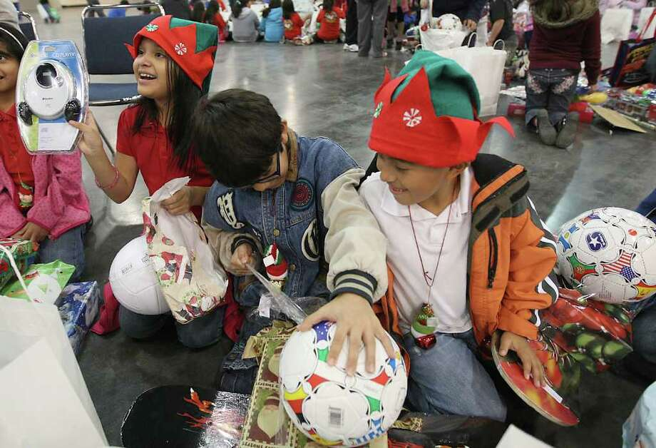 Pilgrim Academy student, Luis Francisco, 9, center, tears into his gifts, while William Vasquez, 9, watches him during the Navidad En El Barrio Children's Events, at the George R. Brown Convention Center, Dec. 17, 2011, in Houston. Photo: Karen Warren, Houston Chronicle / © 2011 Houston Chronicle