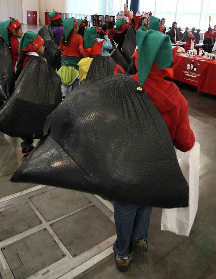 Pilgrim Academy students resemble tiny elves as they pack their gifts out after the Navidad En El Barrio Children's Events, at the George R. Brown Convention Center, Dec. 17, 2011, in Houston. Photo: Karen Warren, Houston Chronicle / © 2011 Houston Chronicle