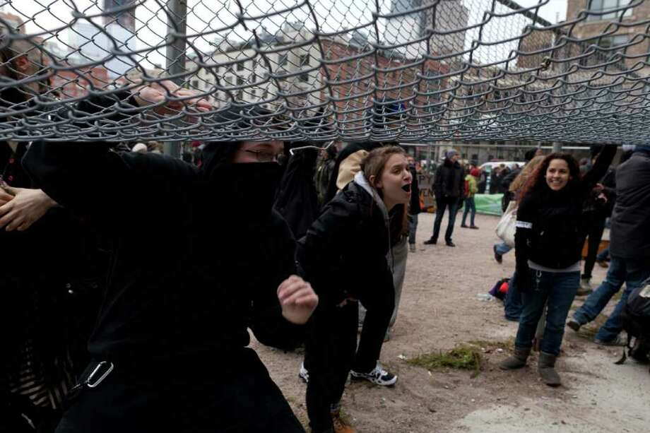 "Occupy Wall Street protestors lift the fences surrounding a park near Duarte Square in an effort to occupy the space they were previously removed from weeks prior, Saturday, Dec. 17, 2011, in New York. While officers made arrests, protesters chanted obscenities and screamed: ""Make them catch you!"" About a thousand people gathered across the street at a city-owned park. Photo: John Minchillo, Associated Press / FR170537 AP"