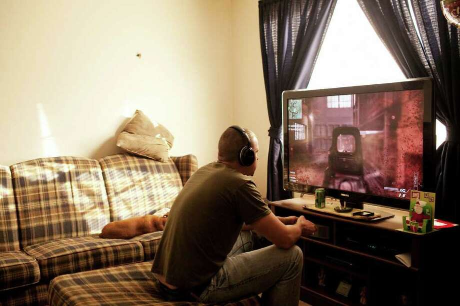 ANDREW SPEAR : NEW YORK TIMES  IDLE TIME: Cpl. Clayton Rhoden, a veteran who is struggling to find employment, plays the video game Call of Duty: Modern Warfare 3 at home in Columbus, Ohio. Photo: ANDREW SPEAR / NYTNS