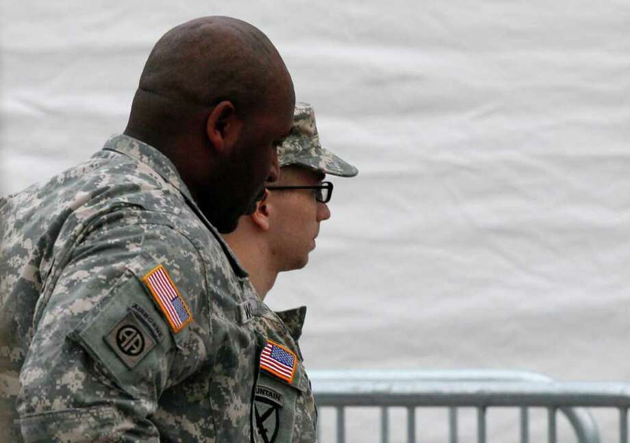 Army Pfc. Bradley Manning, right, is escorted into a courthouse in Fort Meade, Md., Saturday, Dec. 17, 2011, for a military hearing that will determine if he should face court-martial for his alleged role in the WikiLeaks classified leaks case. Manning is suspected of being the source in one of the largest unauthorized disclosures of classified information in U.S. history. (AP Photo/Patrick Semansky) Photo: Patrick Semansky / AP