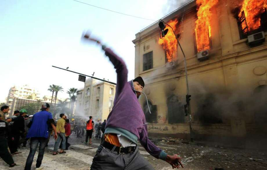 An Egyptian protester throws a stone toward soldiers, unseen, as a building burns during clashes near Tahrir Square, in Cairo, Egypt, Saturday, Dec. 17, 2011. Hundreds of Egyptian soldiers swept into Cairo's Tahrir Square on Saturday, chasing protesters and beating them to the ground with sticks and tossing journalists' TV cameras off of balconies in the second day of a violent crackdown on anti-military protesters that has left nine dead and hundreds injured. (AP Photo/Ahmad Hammad) Photo: Ahmad Hammad / AP