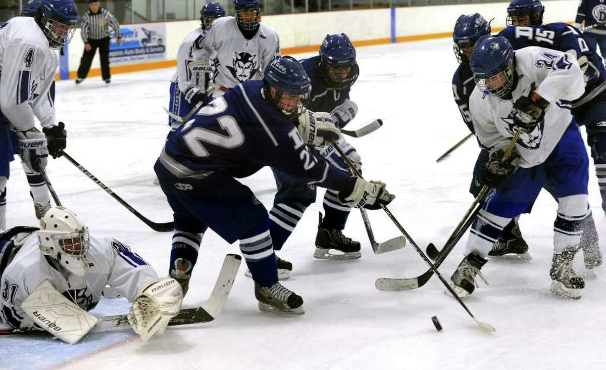 Darien's #22 George Gregory, center, tries to get to the puck as West Haven's #24 Adam Mink, right, looks to intercept, during boys hockey action in West Haven, Conn. on Saturday December 17, 2011. At left is West Haven goalie Justin Shepard.