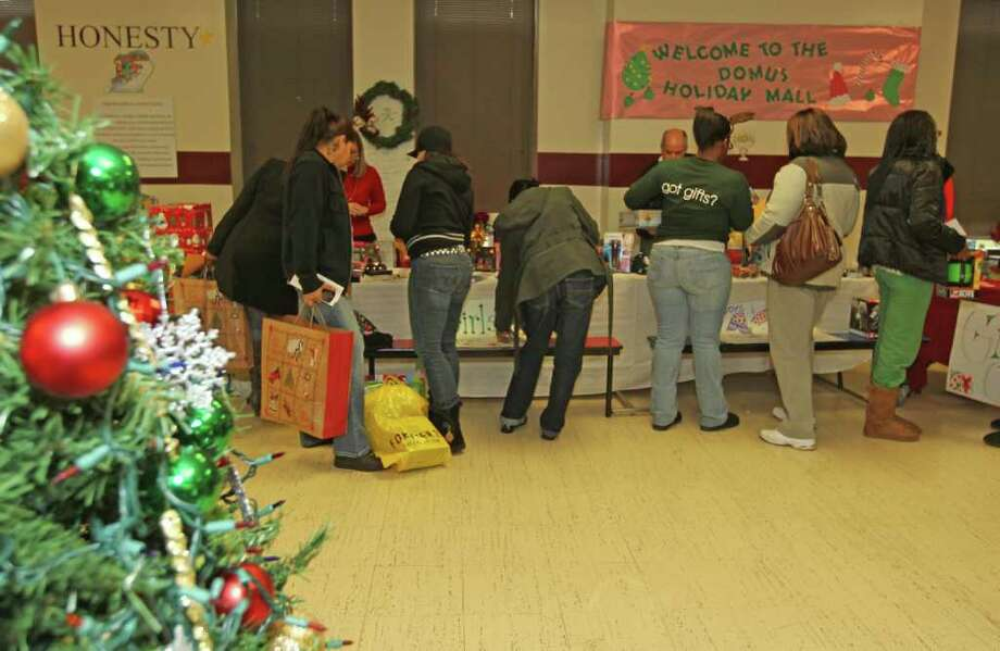 "The Domus Charter School of Stamford held a ""Shopping Mall"" where participants can get free shopping gifts on Saturday afternoon in the schools caferteria. Led by dozens of volunteers who help guide, shop and wrap Christmas presents for those that might do without, the packed event spoke volumes of Christmas cheer and sharing. Photo: J. Gregory Raymond / J. Gregory Raymond/Stamford Advocate Freelance"