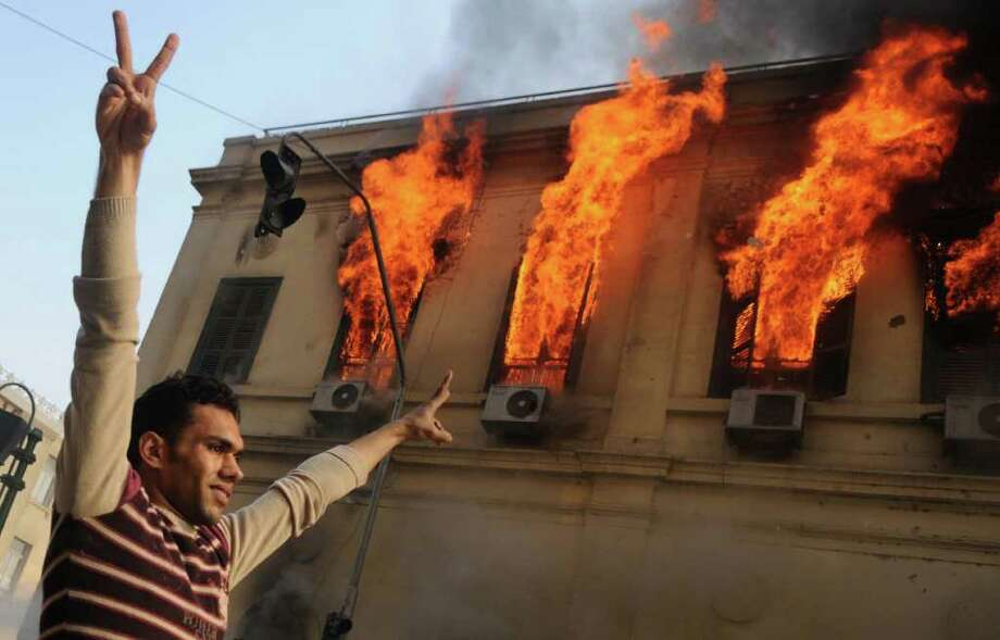 An Egyptian demonstrator makes victory signs near a burning building on December 17, 2011 as violence raged in the administrative heart of Cairo with troops and police deploying in force after clashes with protesters against military rule killed at least eight people. Photo: MOHAMMED HOSSAM, Getty / AFP