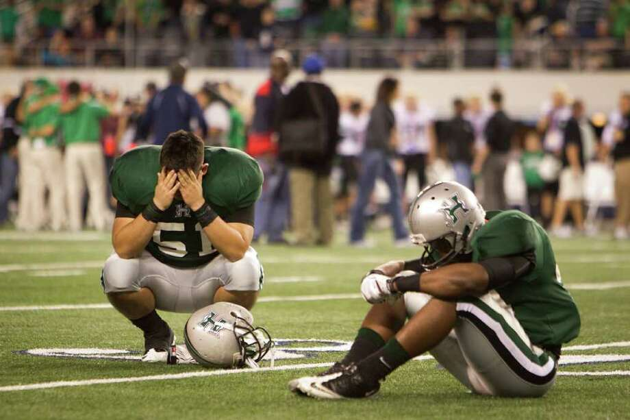 Hightower defensive lineman vincent Rodriguez (51) collects himself while sitting on the field with teammates following the 5A Div. 1 state championship high school football game at Cowboys Stadium on Saturday, Dec. 17, 2011, in Arlington. Southlake Carroll won the game 36-29. Photo: Smiley N. Pool, Houston Chronicle / © 2011  Houston Chronicle
