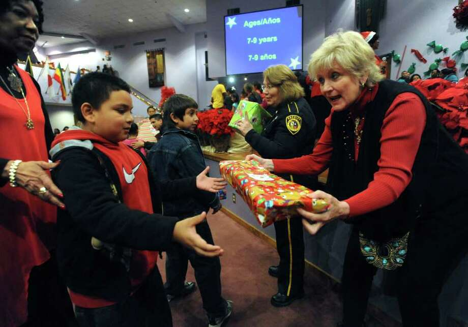 Bexar County District Attorney Susan Reed, right, passes out toys during the 15th annual Jarel's Toy Chest giveaway at New Life Christian Center on Saturday, Dec. 17, 2011. Photo: BILLY CALZADA, Billy Calzada/gcalzada@express-news.net / gcalzada@express-news.net