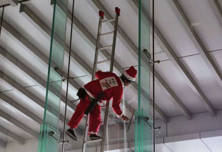 A member of staff wearing a Santa Claus outfit cleans the glass on December 17, 2011 in Tokyo, Japan. Photo: Lintao Zhang, Getty / 2011 Getty Images